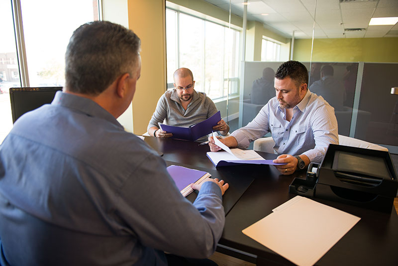 Three GBK Financial team members reviewing client application form